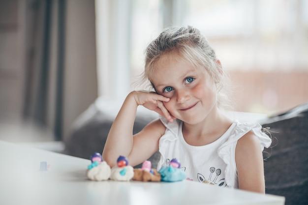 Kleines niedliches vorschulkindkind, das lernspiele mit plastilinfiguren spielt, die für schule vorbereiten