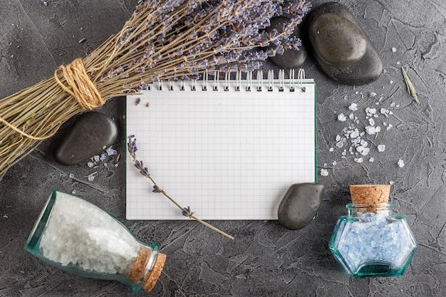 Kleines notizbuch, lavendel, mineralisches meersalz und zensteine auf grauem steinhintergrund. draufsicht.