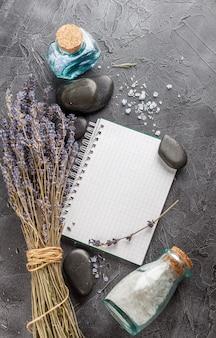Kleines notizbuch, lavendel, mineralisches meersalz und zensteine auf grauem steinhintergrund.