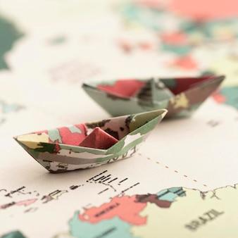 Kleines origami-boot auf dem hohen winkel der weltkarte