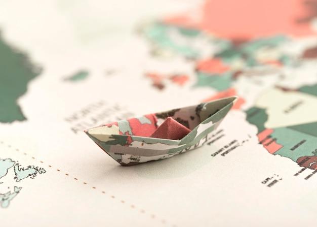 Kleines origami-boot auf weltkarte