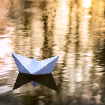 Kleines papierboot, das hinunter den fluss im herbst bei sonnenuntergang segelt. konzept der einsamkeit, verlassenheit