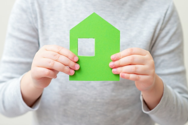 Kleines papierhaus in kinderhänden