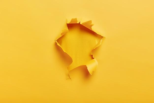 Kleines papierloch mit zerrissenen seiten über gelbem raum für ihren text