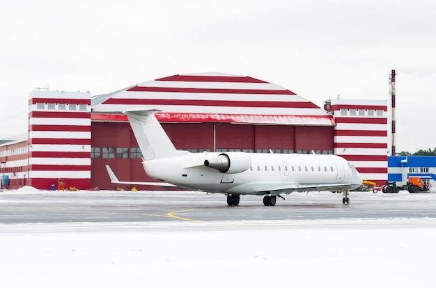 Kleines passagierflugzeug neben dem hangar