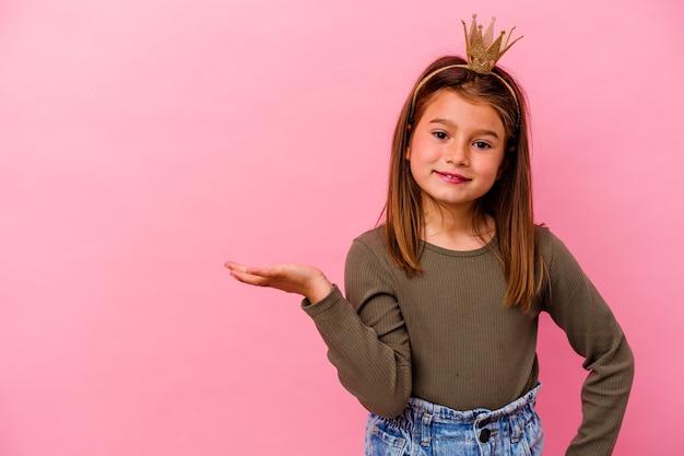 Kleines prinzessinnenmädchen mit der krone lokalisiert auf rosa, die einen kopienraum auf einer handfläche zeigt und eine andere hand auf taille hält.