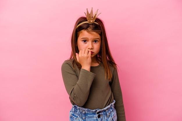 Kleines prinzessinnenmädchen mit krone einzeln auf rosafarbenem hintergrund beißende fingernägel, nervös und sehr ängstlich.