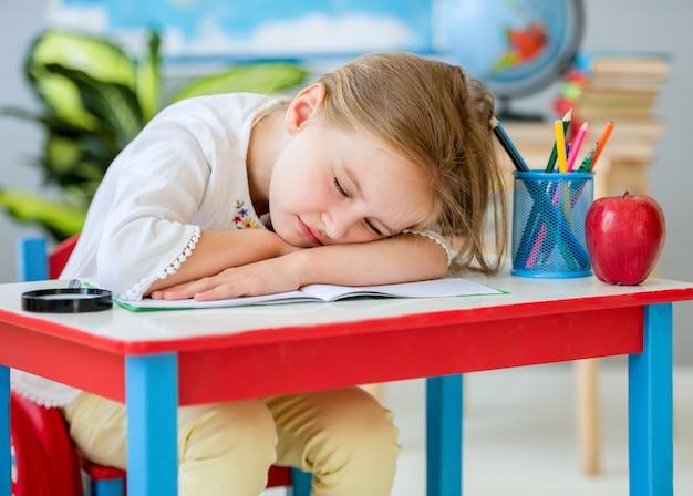 Kleines recht blondes mädchen, das auf dem weiß-roten schreibtisch im klassenzimmer schläft