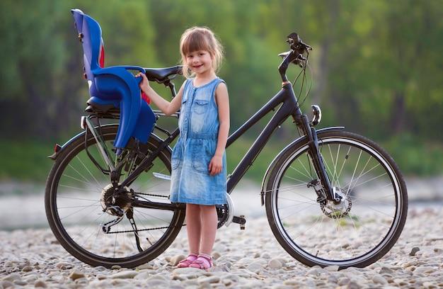 Kleines recht blondes mädchen im blauen kleid, das vor fahrrad mit kindersitz steht