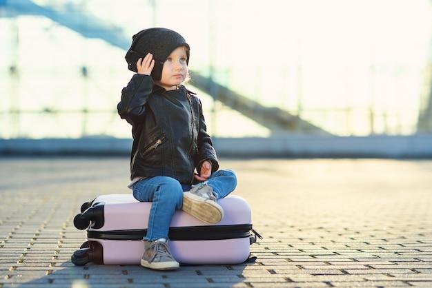 Kleines reisendes mädchen sitzt auf rosa koffer und spricht auf smartphone nahe flughafen gegen sonnenuntergang.