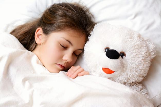 Kleines reizendes mädchen mit gesunder haut des langen dunklen haares liegt auf bequemem bett mit ihrem lieblingsspielzeug. das kleine mädchen, das mit ihrem teddybären unter der weißen warmen decke schläft, hat angenehme träume nachts