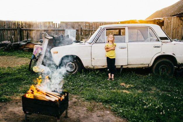 Kleines reizendes süssemädchen mit dem wichtigen gesicht, das an gebrochenem auto der alten weinlese im landschaftsgericht steht. herbstwochenende. sonnenuntergang sonnenlicht. verwirrung im freien. grill mit brennendem brennholz. ländlicher kinderlebensstil