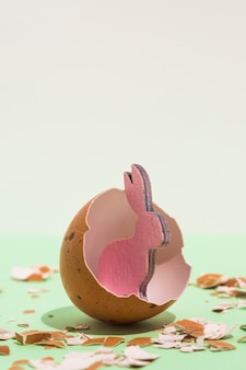 Kleines rosa hölzernes kaninchen im defekten ei