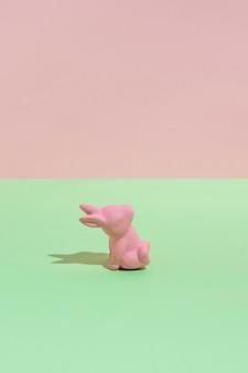 Kleines rosa spielzeugkaninchen auf grüner tabelle