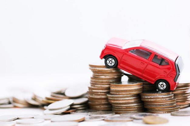 Kleines rotes auto über viel geld gestapelte münzen. für bankdarlehen kostet finanzierung. versicherung, kauf von autofinanzierungskonzept. kaufen und zahlen in raten anzahlung ein auto.