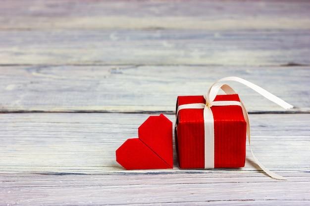 Kleines rotes geschenk gebunden mit weißem band und einer notiz in form eines herzens