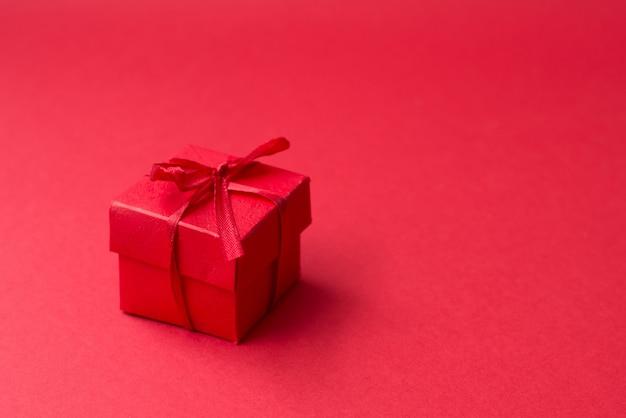 Kleines rotes geschenk mit bogen auf rot. freier copyspace für ihren text. grußkarte