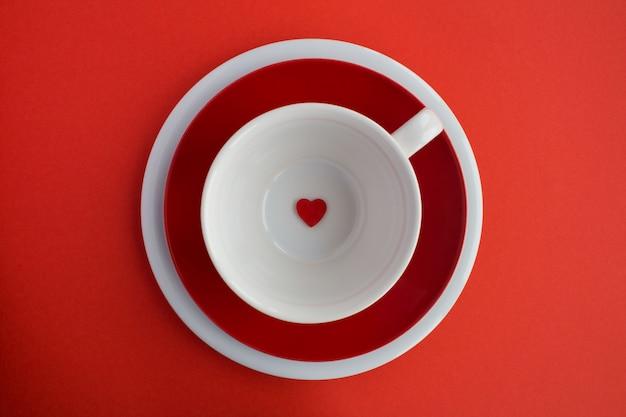 Kleines rotes herz auf der leeren weißen tasse auf der roten oberfläche .diet minimales konzept.