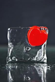Kleines rotes herz eingefroren in einem eiswürfel. schmelzendes eis, wasser.
