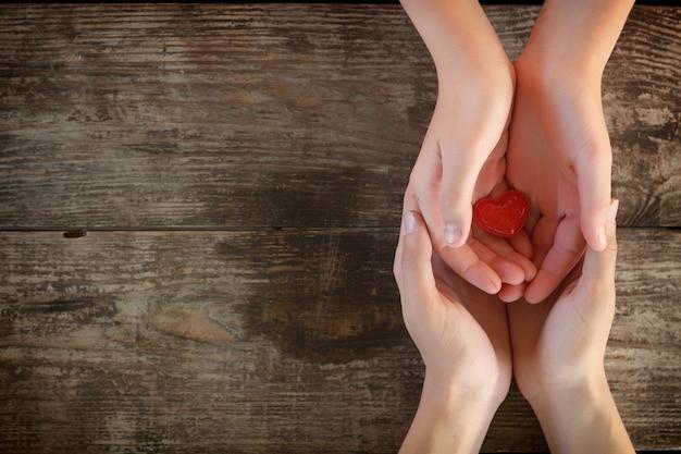 Kleines rotes herz liegt in den händen von männern und frauen, dem begriff der liebe und der romantik.