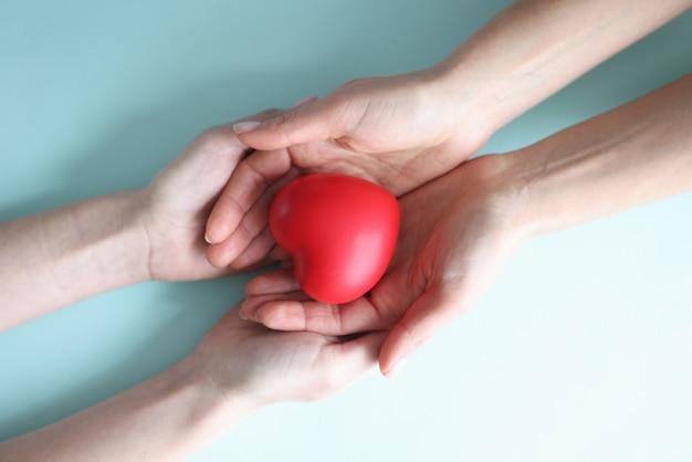 Kleines rotes herz liegt in den händen von zwei menschen