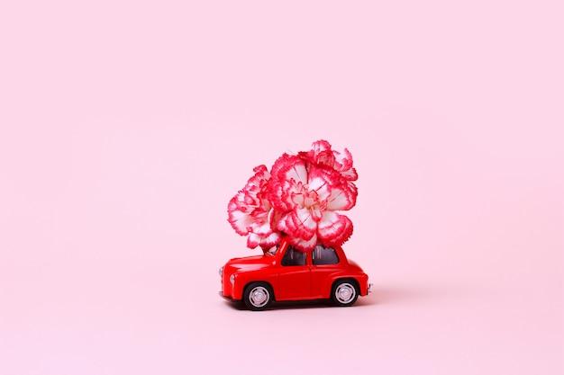 Kleines rotes retro-spielzeugauto mit blume auf dem dach lieferung von geschenken für valentinstag-weltfrauen-tag