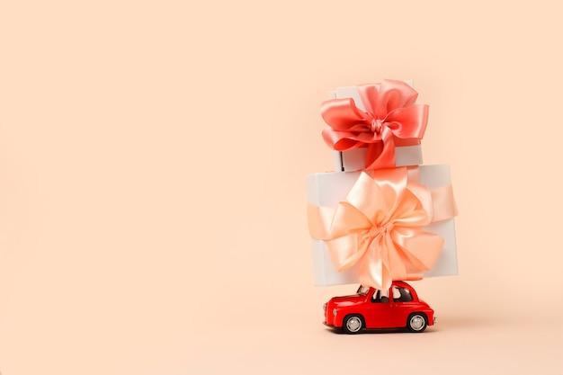 Kleines rotes retro-spielzeugauto mit einem großen geschenk auf dem dach auf kolal lieferung von geschenken für valentinstag-weihnachtswelt-womens day-konzept