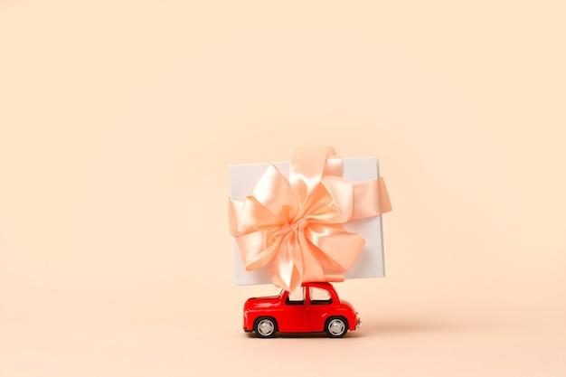 Kleines rotes retro-spielzeugauto mit geschenk auf dem dach auf korallen-neujahrs-weihnachts-valentinstag-weltfrauen-tagesgeschenklieferung