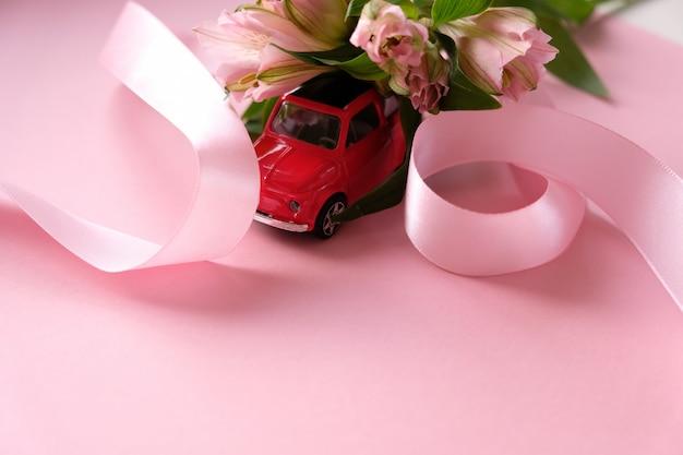 Kleines rotes spielzeugauto trägt einen blumenstrauß von rosa blumen
