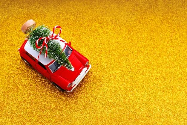 Kleines rotes spielzeugauto und weihnachtsbaum auf glitzergold. draufsicht