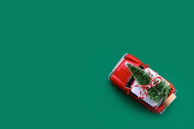 Kleines rotes spielzeugauto und weihnachtsbaum auf grün. draufsicht
