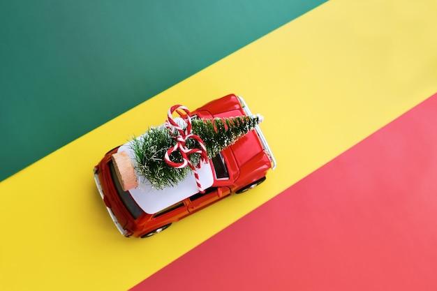 Kleines rotes spielzeugauto und weihnachtsbaum auf grün, rot und gelb. draufsicht