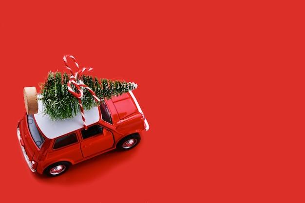 Kleines rotes spielzeugauto und weihnachtsbaum auf rot. draufsicht