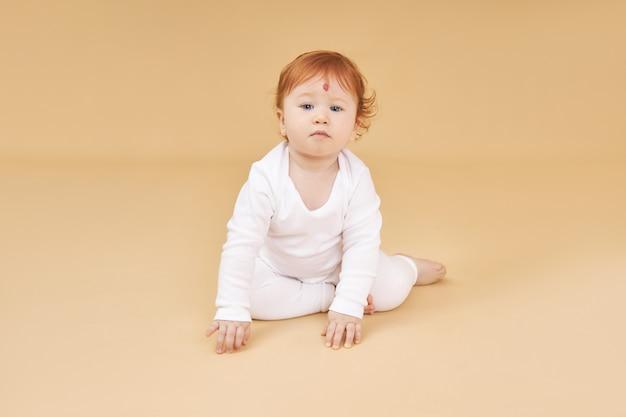 Kleines rothaariges baby spielt auf beige. großer maulwurf auf der stirn, nicht wie alle anderen