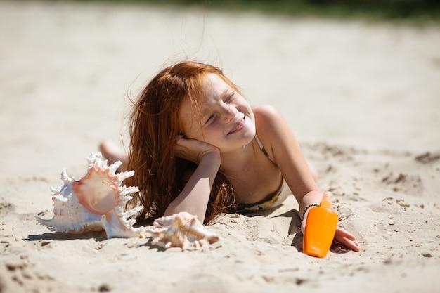 Kleines rothaariges mädchen, das auf dem ein sonnenbad nehmenden sand liegt