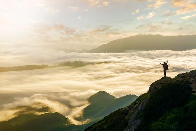 Kleines schattenbild des touristen mit rucksack auf felsigem berg