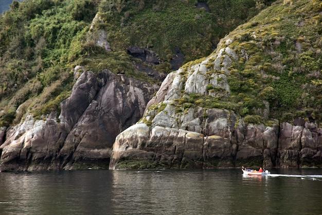 Kleines schiff im see, umgeben von grünen grasbergen