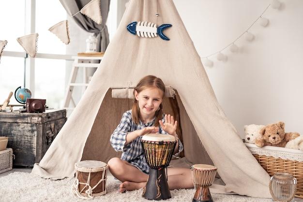 Kleines schlagzeugermädchen, das auf djembe spielt, das zu hause vor ethnischem zelt sitzt