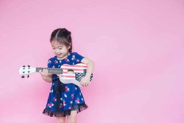 Kleines schönes asiatisches mädchen, das gitarre auf rosa mit kopienraum spielt