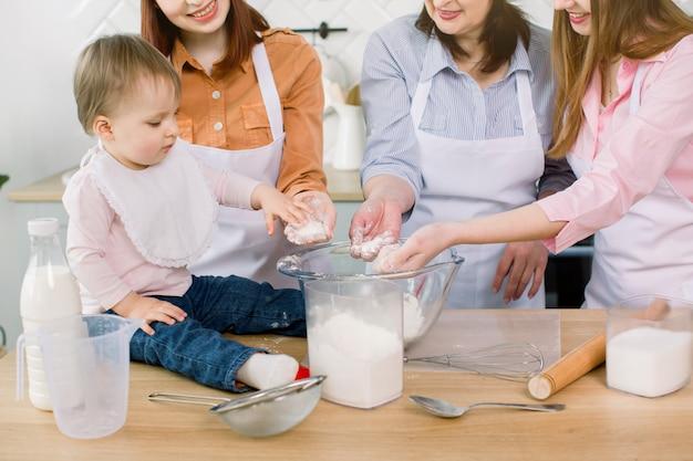 Kleines schönes baby mit mutter, tante und großmutter, die mehl in ihren händen halten und teig zusammen zu hause machen. infant chef backkonzept.