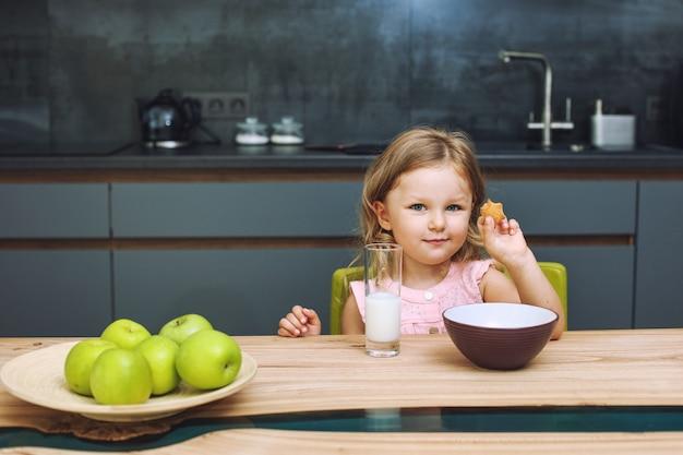 Kleines schönes glückliches baby zu hause in der küche am tisch mit äpfeln und milch