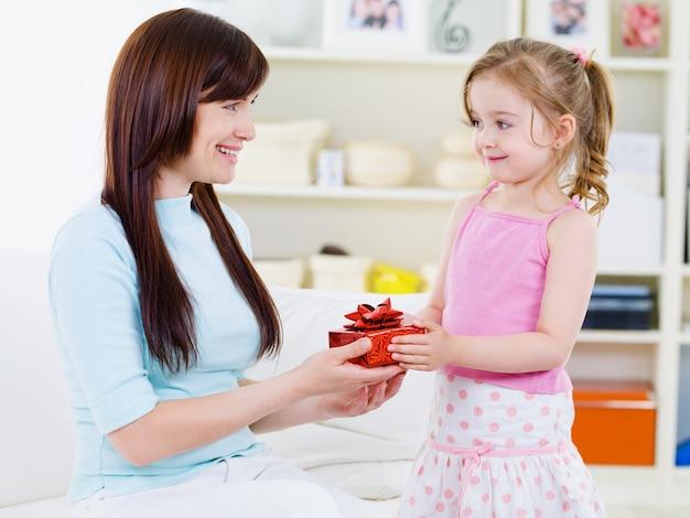 Kleines schönes hübsches mädchen, das ihrer glücklichen mutter ein geschenk gibt