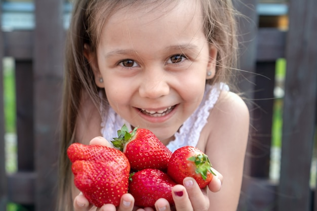 Kleines schönes kind dehnt erdbeeren in ihren händen aus und lächelt. weißes mädchen mit dem langen schwarzen haar, das erdbeeren hält.