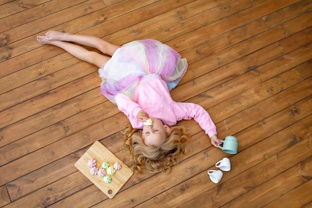 Kleines schönes kindermädchen, das auf holzboden mit bechern und süßen marshmallows liegt