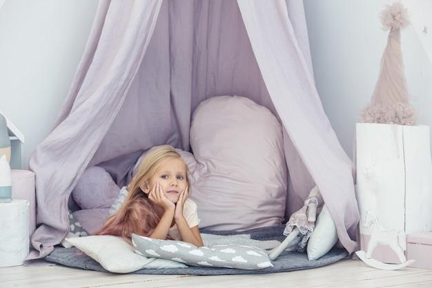 Kleines schönes kindermädchen im kinderspielzimmer, das unter dem zelt spielt