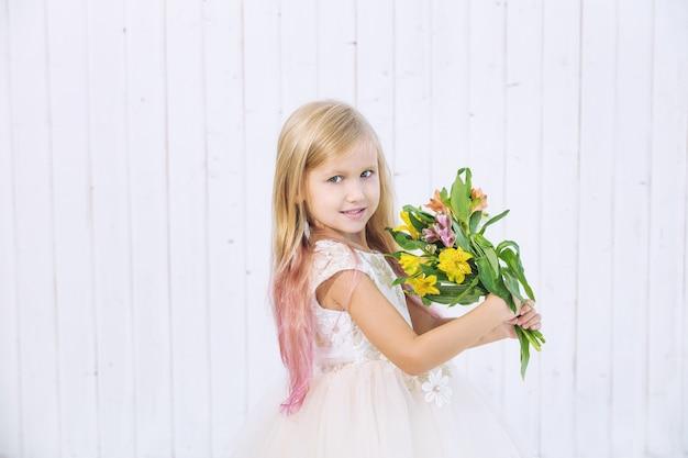 Kleines schönes kindermädchen im schönen kleid mit blumenstrauß auf weißem hölzernem hintergrund