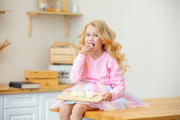Kleines schönes kindermädchen in der küche zu hause glücklich und lustig