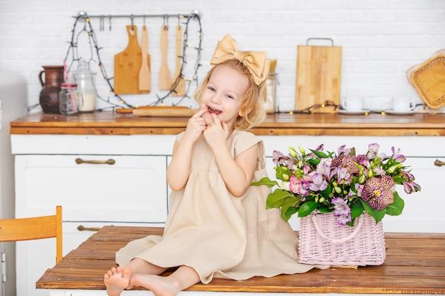 Kleines schönes kindermädchen mit blumen in der küche zu hause