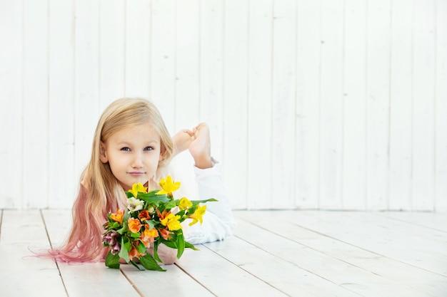 Kleines schönes kindermädchen mit blumenstrauß von hellen farben auf weißem hölzernem hintergrund