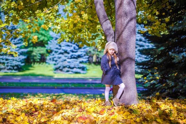 Kleines schönes mädchen auf der herbstwiese nahe großem maplr an einem sonnigen falltag